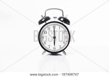 black alarm clock isolated on white table background and reflect.