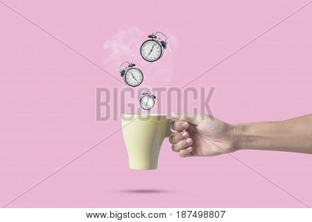 hand holding green coffee cup with alarm clock on pink background. concept drink for time management and creativity imagination inspiration.