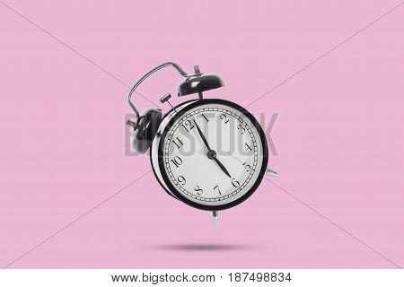 black alarm clock isolated on pink background.