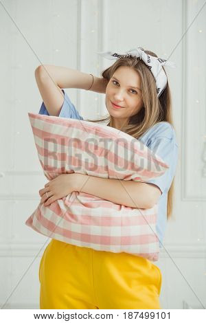 Cheerful woman holds pillow in hands. Girl without make up wants to tidy the room. Sleepy lady with long luxury hair and in headband worn around head as a decoration. Drowsy female hugging big bolster