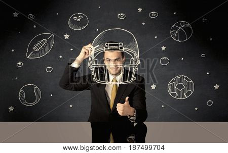 A happy college graduate dreaming about becoming a successful sports person while drawing helmet and ball in space concept