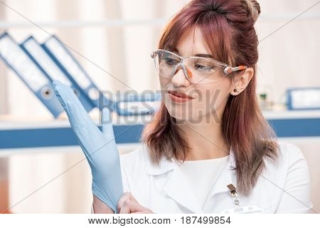 Young Scientist In Lab Coat  Goggles Wearing Medical Glove In Chemical Lab