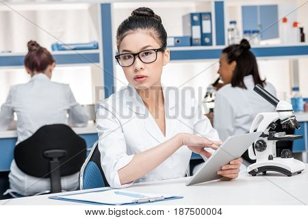Asian Scientist In Lab Coat With Microscope And Digital Tablet Working In Chemical Lab, Scientists G