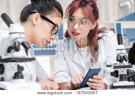 Scientists Working Together With Microscopes And Smartphone In Chemical Lab, Scientists Team Concept