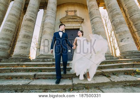 The down view of the happy newlyweds standing near the ancient palace