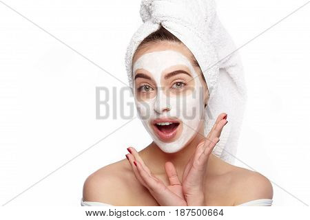 Surprised woman with mouth opened looking at camera with cosmetic mask on her face.