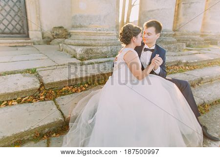 Horizontal photo of the newlyweds holdign hands while sitting on the stairs of the ancient building