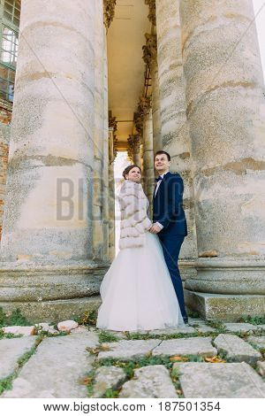 The vertical full-length phot of the newlyweds holding hands between ancient gothic columns