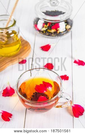 A Cup Of Tea, A Can Of Honey And A Jar With A Black Herbal Floral Tea On A White Wooden Table. Top V