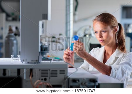 Portrait of a female researcher doing research in a lab, using a tablet computer for data collection and visualization(shallow DOF; color toned image)
