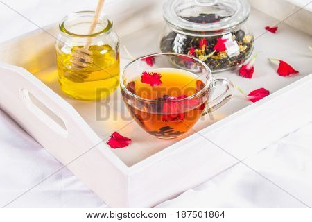 A Cup Of Tea, A Can Of Honey And A Jar Of Black Herbal Tea On A White Tray In Bed.