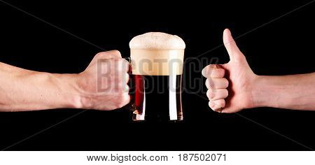 A mug of black beer in guys hand. Isolated background