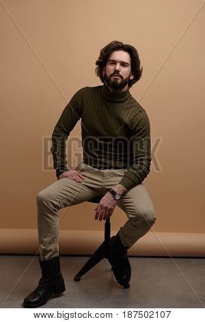 Vertical studio shot of handsome adult businessman sitting on stool and looking at camera with confidence.