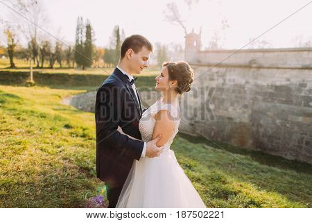 The horizontal side portrait of the smiling newlywed couple hugging near the mansion in the spring