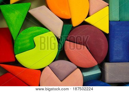 The colored wooden cubes for children on the table. The colored blocks of wood on the table. Abstract objects, mosaic, puzzle for the development of mental abilities, logical thinking
