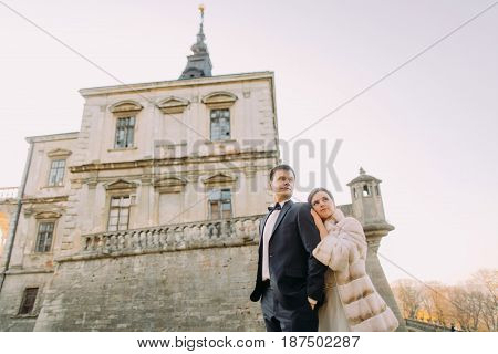 The down side view of the bride leaning on the groom at the background of the gothic palace