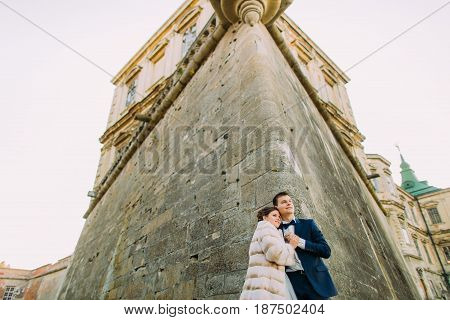 Down side view of the hugging newlyweds leaning on the walls of the ancient castle.