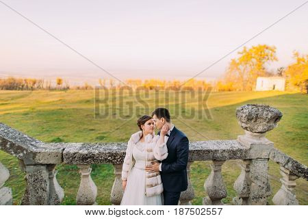 The bride is petting the face of the groom. The sensitive outdoor portrait
