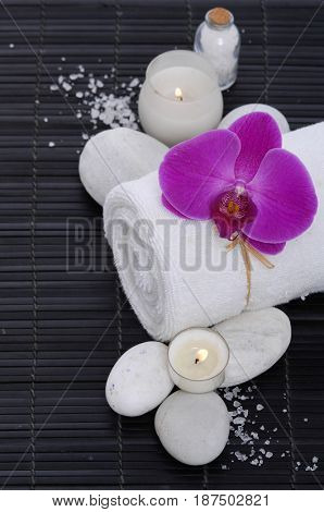 Spa setting with orchid, towel, candle,stones, salt