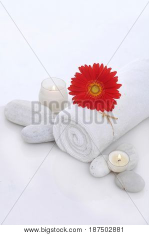 Spa setting with candle, stones,towel, gerbera