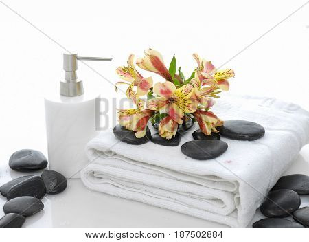 Pile of black stones ,oil and yellow orchid on towel –white background