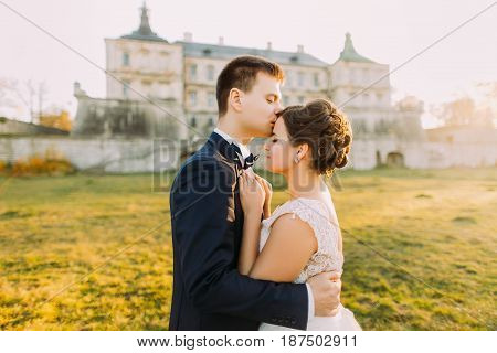The groom is kissing the beautiful bride in the forehead at the background of the antique gothic castle. during the sunset