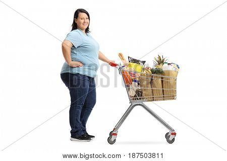 Full length portrait of a woman with a shopping cart waiting in line and looking at the camera isolated on white background