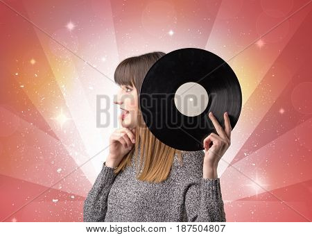 Young lady holding vinyl record on a red background with lights shining behind her