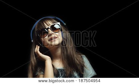 Studio shot of cute teenager girl wears headphones and sunglasses before black background, listening rhytmical music, youth freedom concept