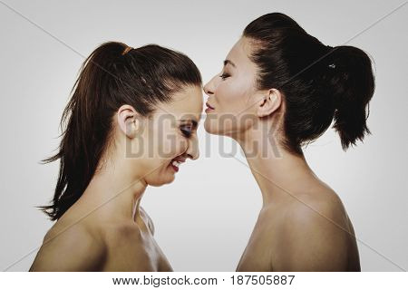 Woman kissing friend in forehead.