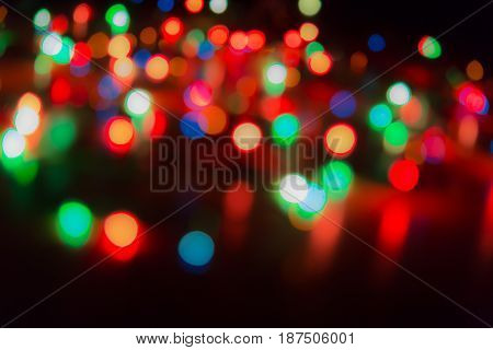 Blurry abstract colorful background. Colored Christmas garland. Bokeh and defocusing of the lens