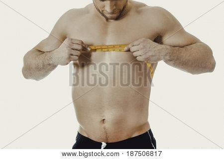 Muscular man measuring his chest.