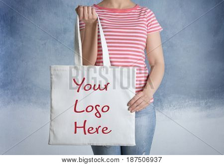 Woman holding shopping bag with space for logo on color background