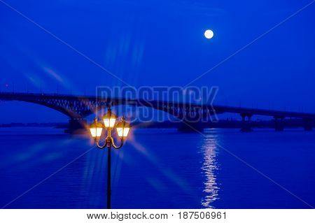 Road bridge between the cities of Saratov and Engels in the twilight. Full moon. A street lamp.