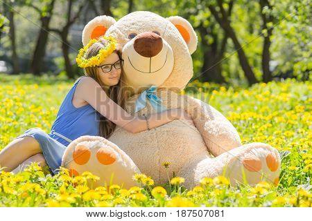 girl with teddy bear sitting on dandelion meadow