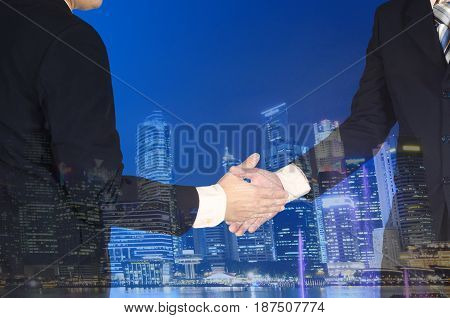 Double Exposure Of Businessman Shaking Hand On Blurred City Background.