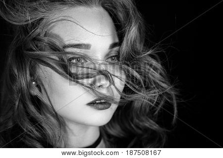 luxury woman with flying long hair on black background, monochrome
