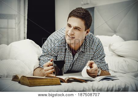 Happy man with a book in his bed.
