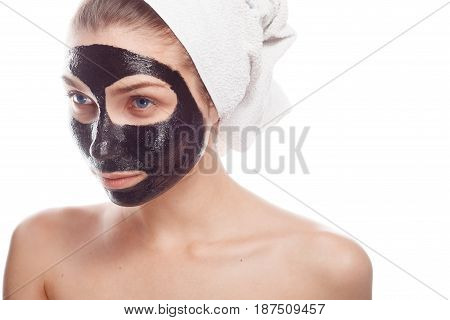Pretty woman with black clay mask applied on her face isolated on white.