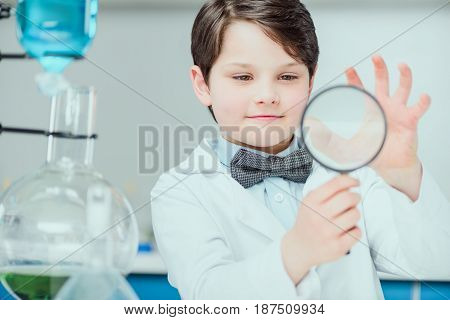 Little Scientist In White Coat Holding Magnifier In Chemical Lab, Science School Concept