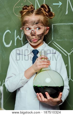 Portrait Of Girl In White Coat Holding Flask With Chalkboard Behind In Science Laboratory