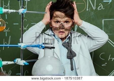 Shocked Boy In White Coat And Protective Glasses After Experiment In Science Laboratory