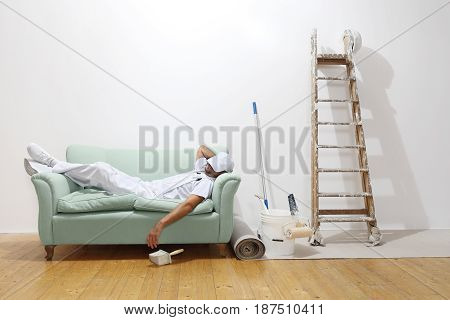 Very tired worker concept painter man sleeps on the couch
