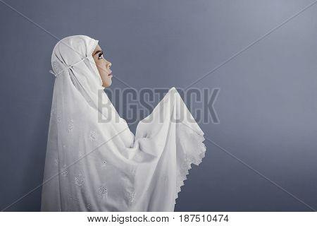 Side View Of Asian Muslim Woman Wearing Veil Praying
