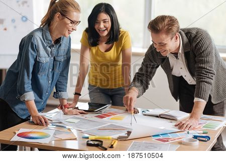 Creative work. Positive professional hard working colleagues standing around the table and working together while developing a new design