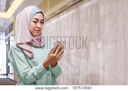 Beautiful Asian Woman With Hijab Holding Smartphone
