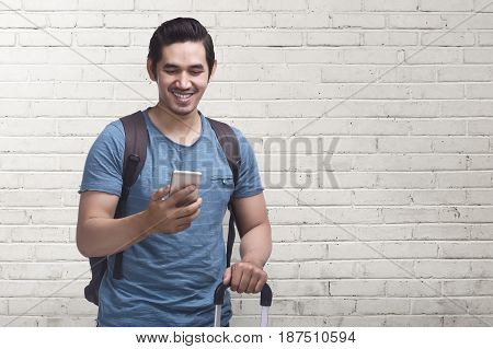 Young Asian Man Journey With Mobile Phone Carrying Suitcase