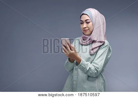 Young Asian Muslim Woman In Hijab With Her Smartphone