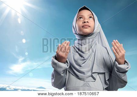 Religious Asian Muslim Kid Raising Hand And Praying