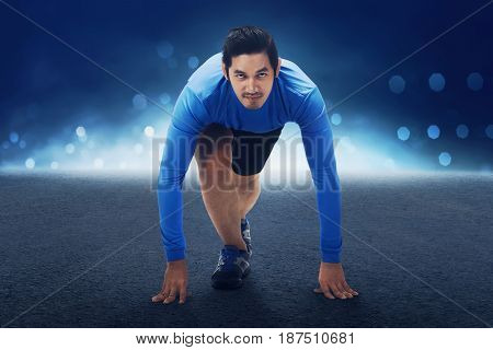 Runner Asian Man With Hands On Starting Line Ready To Sprint